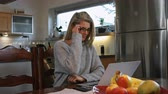 čtyřicátá léta : A woman working at home on her computer smiles for the camera and takes off her glasses.