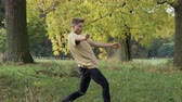 full body shot : A male dancer dancing a modern dance in an autumnal park. Full body shot. Stock Footage