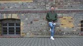 full body shot : A male model standing by a brick wall dressed in street wear. Full body shot. Stock Footage
