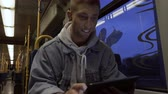 facing : A happy young man using a digital tablet while commuting in a tram. Medium shot. Low angle. Front facing.