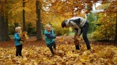 tossing : Childhood moments: children and teenager playing with autumn leaves in park. Selective focus. Full body shot. Slow motion.