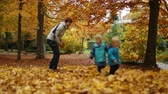 rodzeństwo : Childhood moments: Teenager and children playing with autumn leaves in a park. Full body shot. Rack focus. Slow motion.