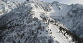 passo : An Italian Alps ski slope filmed from the air on a bright and sunny winters day. Drone shot.