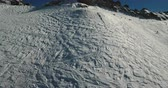passo : Snowy terrain on a ski slope. Skiers and adventure seekers go about their business below. Drone shot.