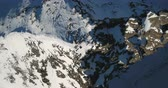 ragged : Overhead of mountain terrain. Snow covered rocks and adventure seekers below. Aerial shot. Stock Footage