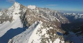 passo : Beautiful mountain peaks on a sunny winter day. A group of adventure seekers stand beside a cross on a rocky jagged mountaintop. Drone shot. Stock Footage