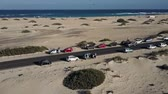 Canary Islands beach panorama. Cars parked on road between sands. Aerial view.