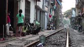 вьетнамский : January, 2018. Hanoi, Vietnam. Train tracks passing through Hanoi slums while children stand on the side. The so called train street is a very narrow street in Hanoi that has train tracks passing through it and where people live right beside the functioni