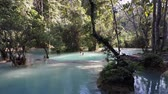 laosz : Kuang Si Falls pools with bathers bathing in the turquoise waters. Wide shot.