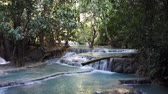 laosz : The famous Kuang Si waterfall in Loas with pools of turquoise colors. Sun shines through the dense tropical foliage.