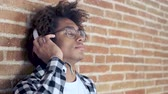 lad : Video of relaxed young african american man listening to music with headphones leaning on stone wall at home. Stock Footage