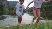 twee mensen : Video of two children holding hands while running out of the mountain lake on a cloudy day.