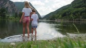 twee mensen : Video of two children holding hands while walking towards the mountain lake on a cloudy day. Stockvideo
