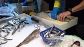 gutting : seller cleans fish scales in the market