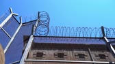 korumalı : high prison fence with barbed wire against a clear sky. bottom view Stok Video
