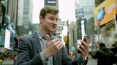 překlad : Cheerful young man having a video chat on Times Square by using his smartphopne
