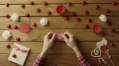 minimalisme : Joyful man with handmade heart of paper sits by table, top view