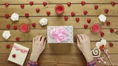 minimalisme : Man puts valentine onto present box, top view
