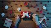 minimalisme : Man puts valentine onto present box for his girlfriend, top view