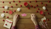 minimalismo : Young man with handmade paper hearts sits by wooden table, top view Stock Footage