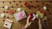 havai : Young man tries to understand what lies inside his holiday gifts and shakes them, top view Stok Video