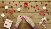 minimalismo : Man with paper hearts sits by decorated table, top view