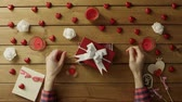 minimalisme : Young man puts spinner into the gift box as holiday present, top view