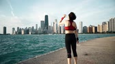 фитнес : Runner athlete looking at skyscrapers and drinking water