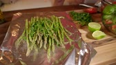 saláta : The woman is cooking fresh and tasty asparagus in the foil. Close view. Sprinkle with lime juice.