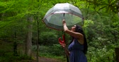 Charming beautiful woman twisting an umbrella in rainy day at beautiful park.
