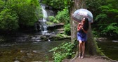 Young woman standing in the forest with an umbrella near waterfall and looks at the falling water. Stock Footage