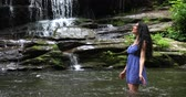 Young woman standing in the river near waterfall and splashes water. Woman is smiling and breathing deeply.