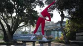 concepcion : Young blonde woman in red latex costume is doing yoga exercises on the table in the forest. Archivo de Video