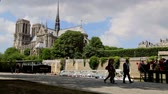 frança : People walking by the Seine with Notre-Dame in BG