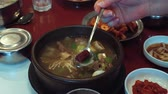 vařené : Hand stirring spoon Korean soup with mushrooms and meat in plate standing on table Dostupné videozáznamy