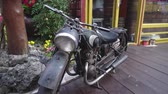 обычай : Parked old-fashioned vintage motorcycle black color standing on wooden floor Стоковые видеозаписи