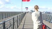 tatarak : The girl is walking along the wharf, the strong wind is blowing, the Russian flag is developing. slow motion. 1920x1080. full hd