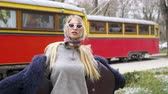 narbe : A girl in modern style clothes in a fluffy cape, posing on the street near the tram, on the background of cars and high houses of the Soviet era Stock Footage