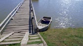 sensual : lonely boat stands moored to a wooden pier on a pond Vídeos