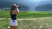 japonês : girls in short white shorts in which there is a phone in the back pocket, take pictures on a professional photo camera, a lake in the mountains with tall trees.