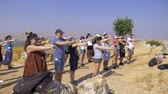 探検家 : Israel Mount Arbel - July 21, 2019. a group of people on doing warm-ups raise their hands to the top