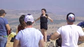 探検家 : Israel Mount Arbel - July 21, 2019. instructor on the mountain shows how to get up to a group of people to charge and squint from the bright sun of Israel
