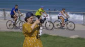 werk zoeken : Israel Tel Aviv - July 21, 2019 woman in a yellow dress takes pictures with a camera Stockvideo