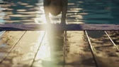 handheld : Girl jumping in swimming pool in GOA in slow motion Stock Footage
