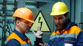 explicando : two electricians at the substation talking on the background of the danger sign. Stock Footage