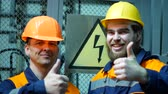 transformador : two electricians at the substation smile near the danger sign.
