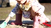 ostrý : A little girl is digging in the sandbox. The Village in Ukraine.