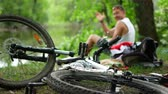 throw away : A dirty bike lies on the ground in the forest. The guy waving his hand in the background Stock Footage