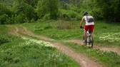 haver : Young man quickly rides a bicycle in the green spring countryside field along the path. Youth sport concept.
