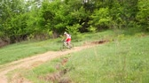 janota : Young man quickly rides a bicycle in the green spring countryside field along the path. Youth sport concept.